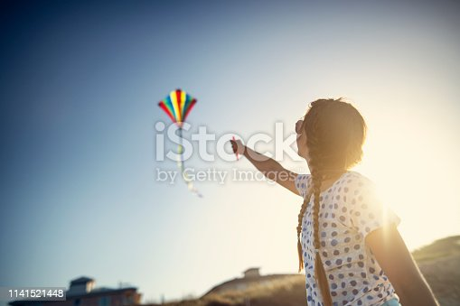 istock Teenage girl flying a kite on a beach 1141521448