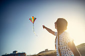 Girl enjoying flying a kite on a beach.\nNikon D850