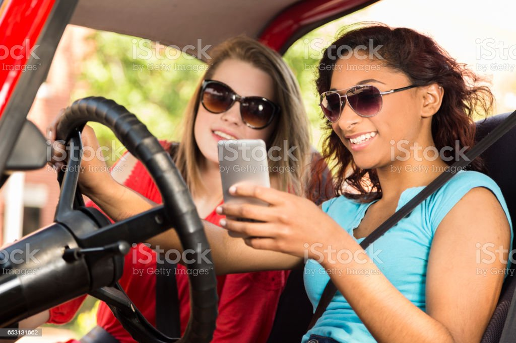 Teenage girl friends take a summer road trip in downtown city area....