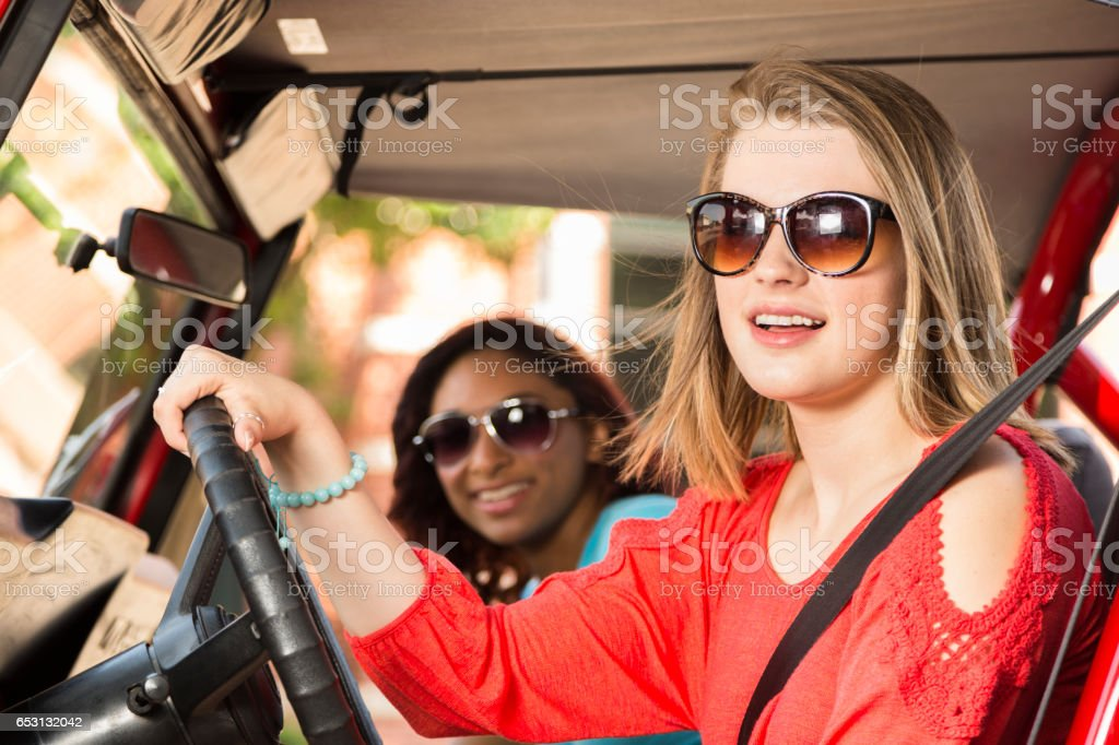 Teenage girl friends take a summer road trip in downtown city area.