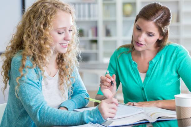 teenager-mädchen bekommt hilfe von hausaufgaben tutor in der schule - geführtes lesen stock-fotos und bilder