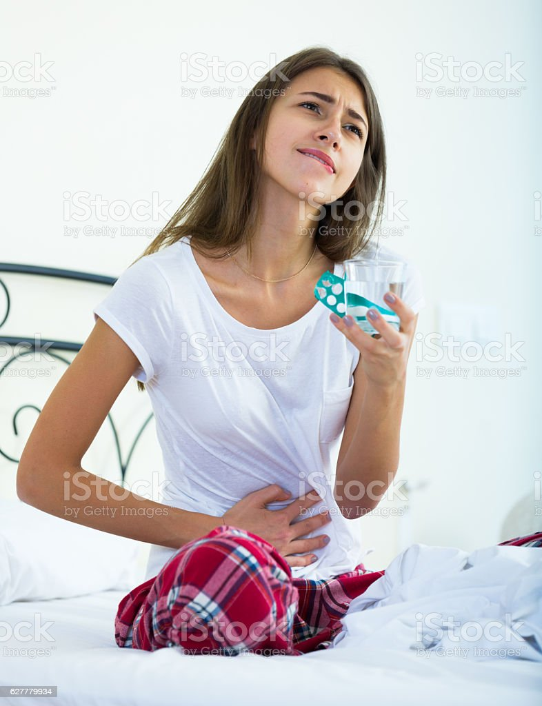 Teenage girl having belly pain and taking pills stock photo