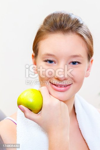 Teenage girl having break after exercising, looking at camera, holding an apple, smiling, posing indoors.