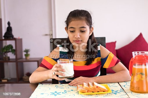 Teenage girl with a glass of milk and morning breakfast at home