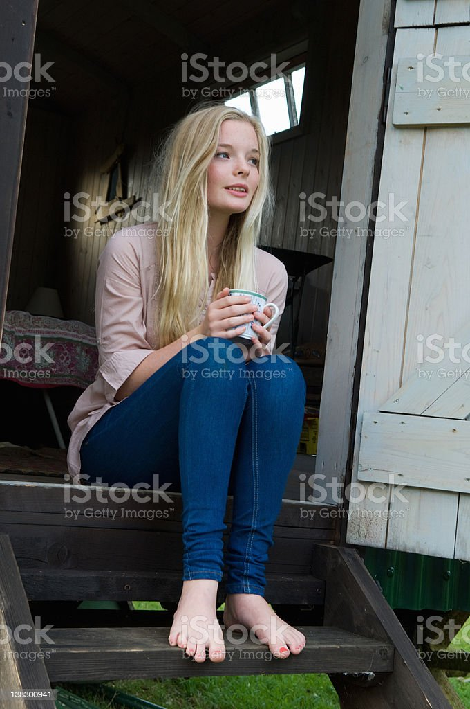 Teenage girl having coffee on doorstep stock photo