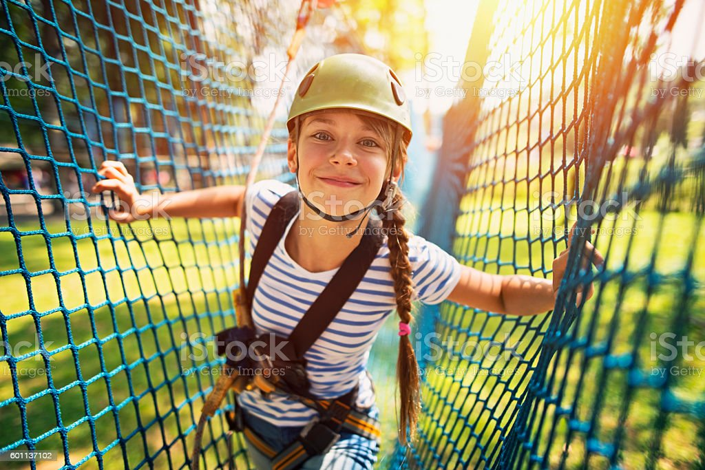 Teenage girl having fun in ropes course adventure park stock photo