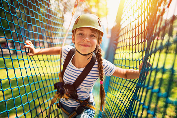 Teenage girl having fun in ropes course adventure park Little girl in ropes course in outdoors adventure park. The girl aged 10 smiling at the camera and walking in a safety net obstacle, leisure equipment stock pictures, royalty-free photos & images