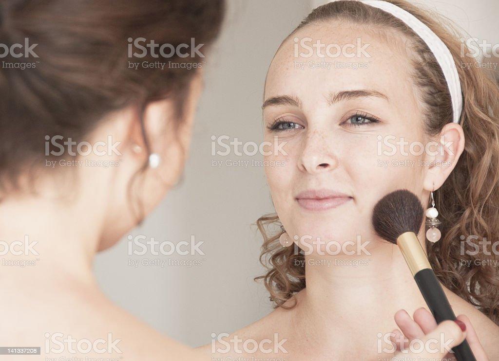 Teenage girl having her makeup done stock photo