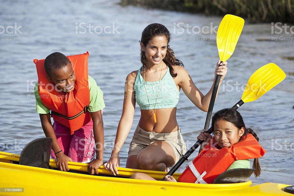 Teenage girl helping children with kayak royalty-free stock photo