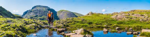 Teenage girl hikers with packs hiking mountain trail wilderness panorama stock photo