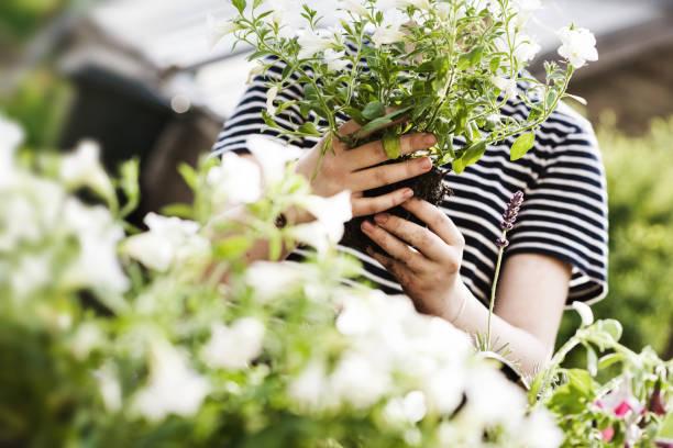 Teenage-Mädchen mit einem Blumentopf mit weißen Blumen für die Pflanzung im Garten – Foto