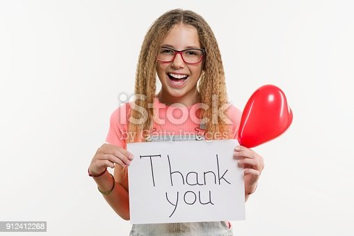 istock A teenage girl holding a paper with a thank you text, and a heart balloon 912412268