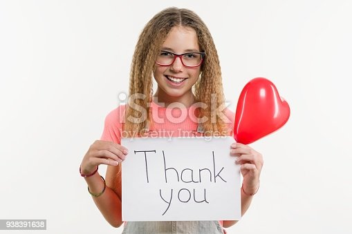 istock Teenage girl holding a paper with text thank you, heart balloon, white studio background 938391638