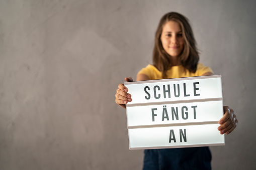 """Teenage girl holding a sign that shows """"School starts"""" in German language, meaning """"School is starting"""""""