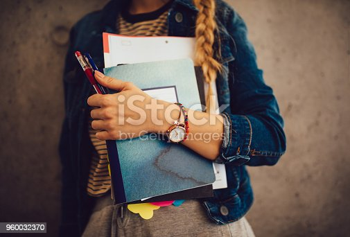 istock Teenage girl holding books, notebooks and pencils standing against wall 960032370