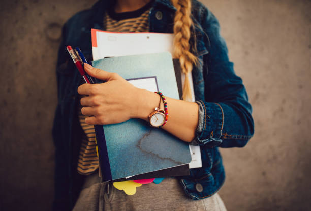 Teenage girl holding books, notebooks and pencils standing against wall stock photo