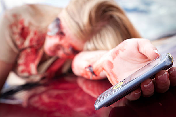 Teenage girl holding out cell phone on car after wreck stock photo