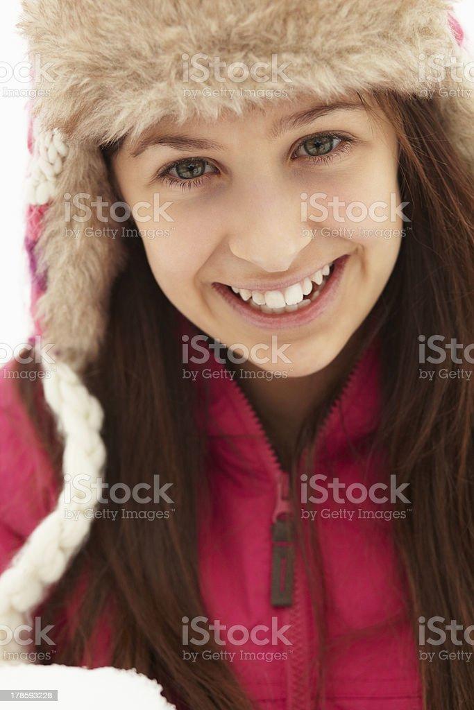 Teenage Girl Holding Snowball Wearing Fur Hat stock photo