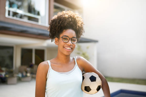 Teenage girl holding soccer ball Teenage holding soccer ball female high school student stock pictures, royalty-free photos & images