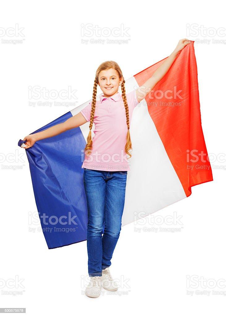 Teenage girl holding unfolded French flag behind stock photo