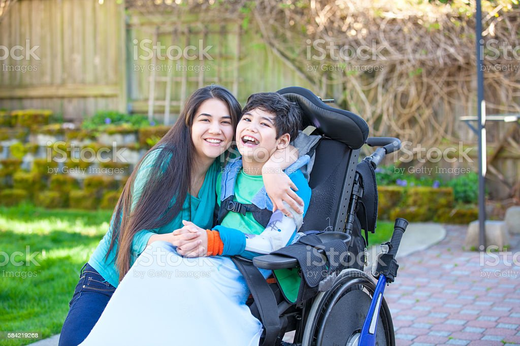 Teenage girl hugging disabled brother in wheelchair outdoors stock photo
