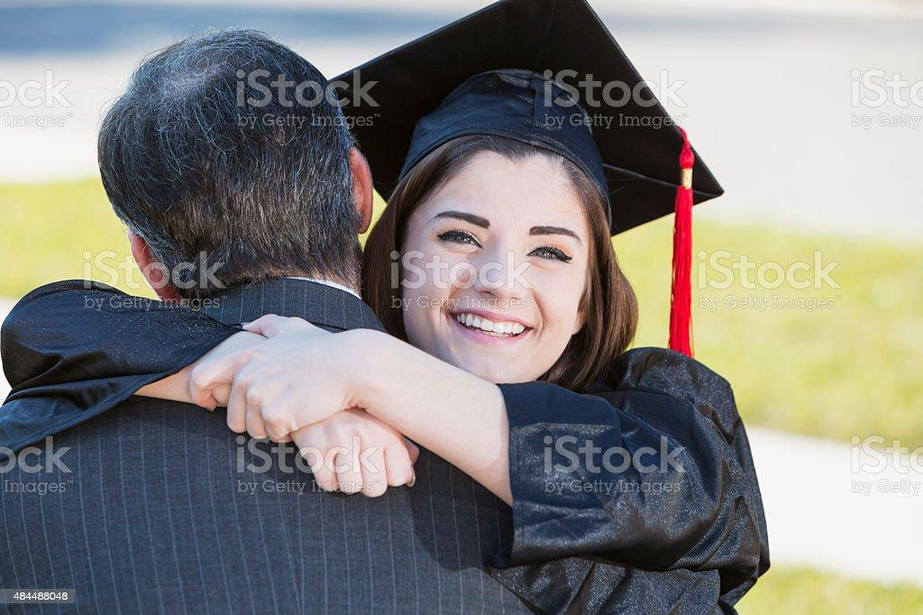 Teenage Girl Hugging Father Wearing Graduation Gown Stock Photo ...