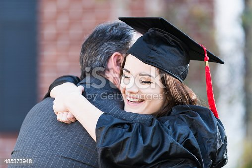 A teenage girl wearing a black graduation cap and gown, hugging her father, She is smiling, with her arms wrapped around her dad's neck, resting her chin on his shoulder, with her eyes closed.  We do not see his face so he is unrecognizable.  He is wearing a dark gray business suit.