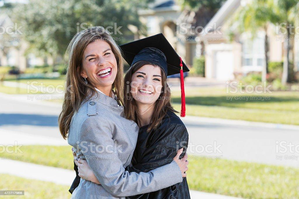 Teenage Girl Hugging Mother Wearing Graduation Gown Stock Photo ...
