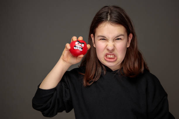 teenage girl imitating facial expression of red angry squeeze ball stock photo