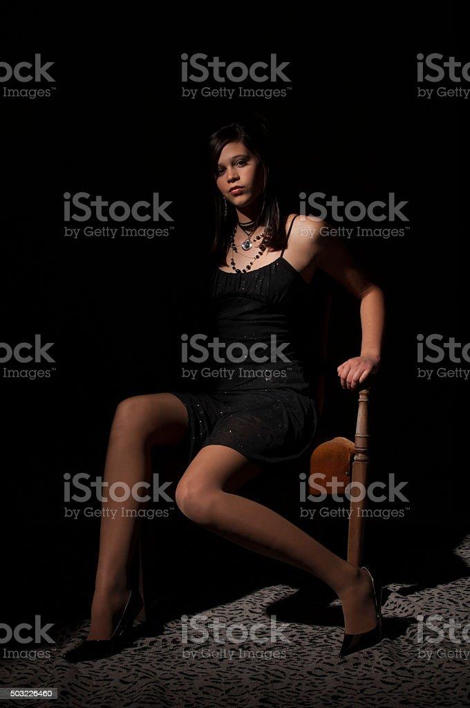 9b5615c112ad Adolescente Ragazza In Un Abito Elegante Nero Seduto Su Una Sedia ...