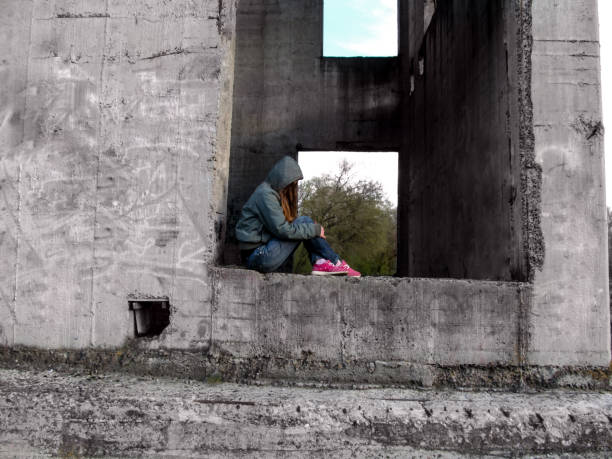 A teenage girl in a hood without a face sits in a rectangular hole of a concrete wall stock photo