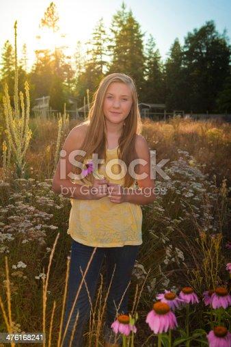 Teenage girl holding an coneflower flower on a suburban yard.