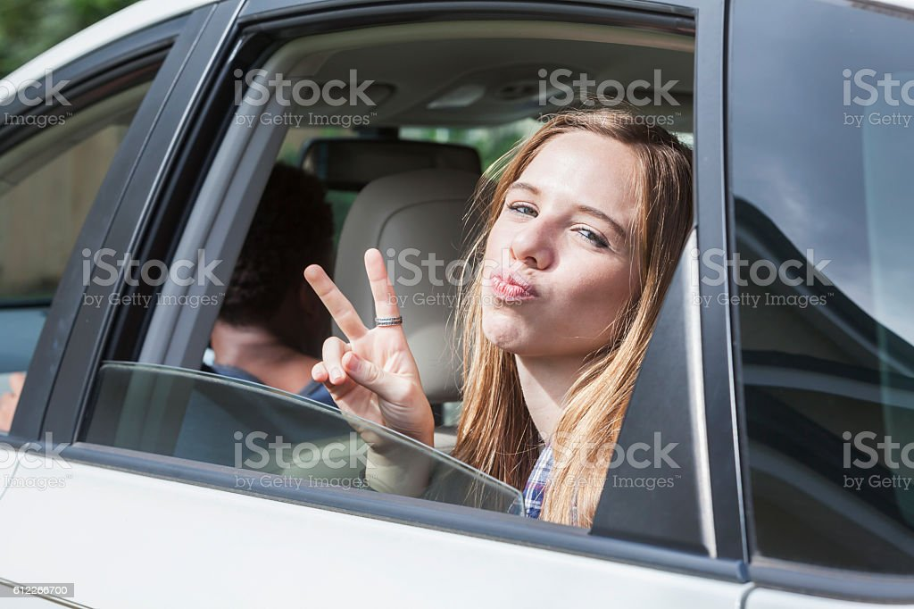 Teenage girl in back seat of car making peace sign stock photo