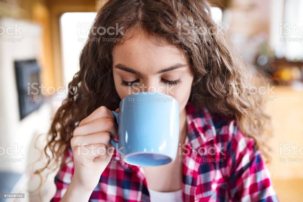 Teenage girl in checked shirt enjoying a cup of coffee stock photo