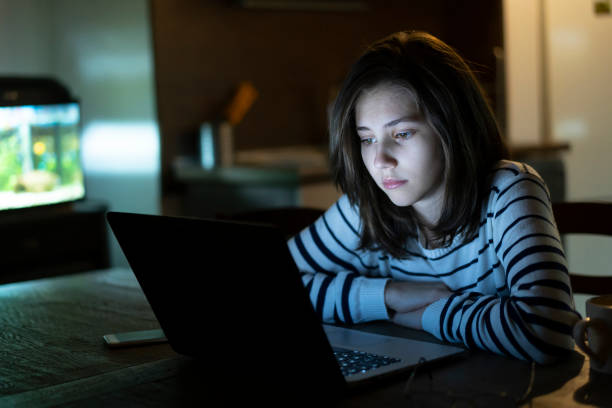 Teenage girl in front of computer late at night