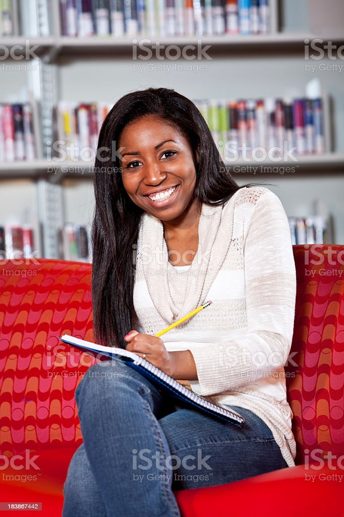 Teenage girl in library writing on notebook royalty-free stock photo