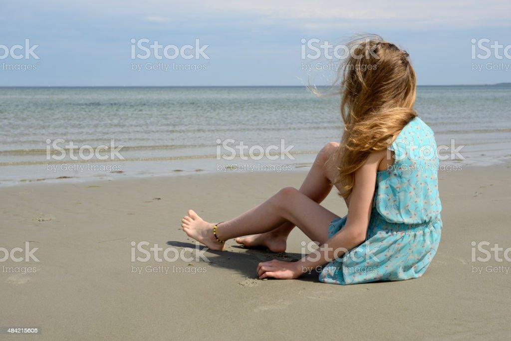 Teenage girl in light blue sundress sitting at the sea stock photo