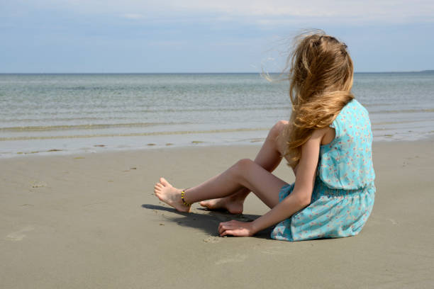 Teenage girl in light blue sundress sitting at the sea stock photo