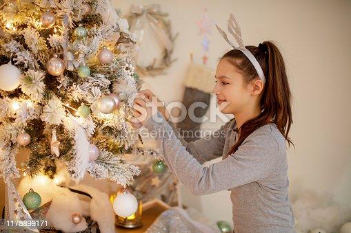 Teenage girl in pajamas and headband hanging ornament on frosty Christmas tree