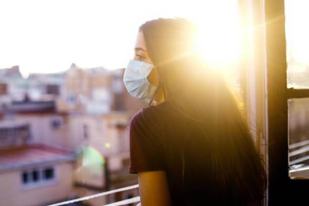 teenager-mädchen in quarantäne trägt schutzmaske blick aus dem fenster bei sonnenuntergang - standbildaufnahme stock-fotos und bilder
