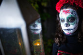 teenage girl in spooky halloween mask with lantern