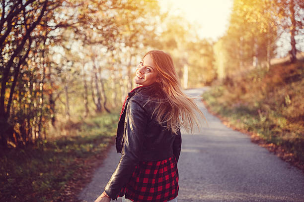 Teenage girl in the autumn park Girl walking among nature and looking back over shoulder looking over shoulder stock pictures, royalty-free photos & images