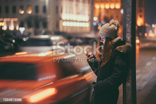 Smiling woman at the street during winter texting for taxi through mobile app
