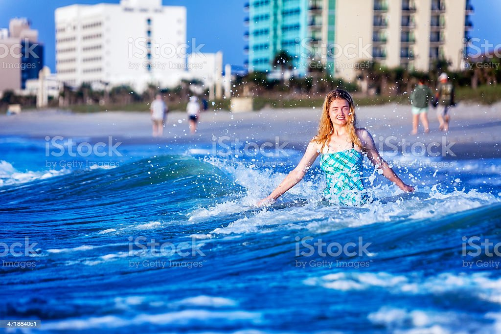 Teenage Girl in Wave Near Beach with Copy Space royalty-free stock photo