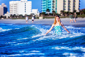 A teenage young woman enjoys the splash of the surf near a beach resort.