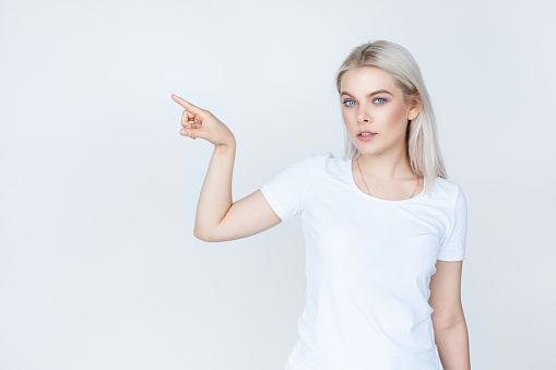 teenage girl in white t-shirt pointing finger away stock photo