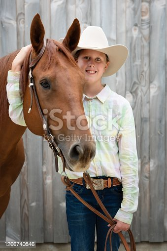 Blonde teenage girl dressed in wild west horseback riding outfit standing side by side next to her horse. Smiling bright and happy to the camera. Real People Horseback Riding Portrait