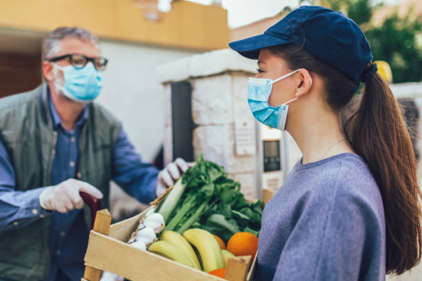 Teenage girl is delivering some groceries to an elderly person, during the epidemic coronovirus, COVID-19. stock photo