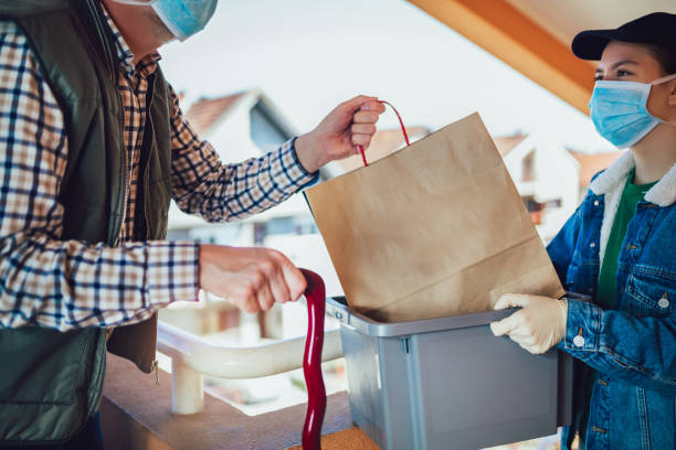 Teenage girl is delivering some groceries to an elderly person. Contactless delivery during the quarantine stock photo