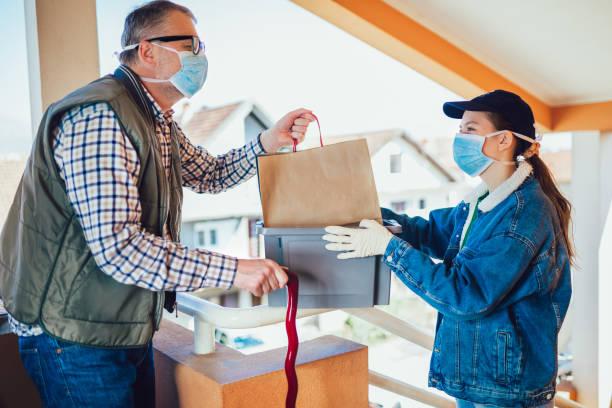 Una adolescente está entregando algunos alimentos a una persona mayor. Entrega sin contacto durante la cuarentena - foto de stock